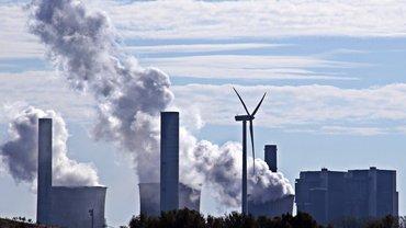 Windkraftanlage vor einem Kohlekraftwerk